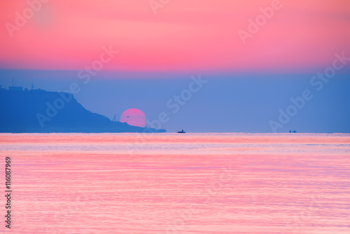 Papiers peints Rose banbon sunrise over the sea. Bright colors huge sun coming out from behind the cape. Dalenko small boat on the horizon. Reflected red light on the water.