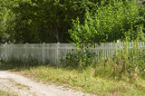 Countryside courtyard fence with white wooden laths