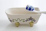 Spazzolino e dentifricio, appoggiati su vasca da bagno in miniatura. Igiene orale quotidiana