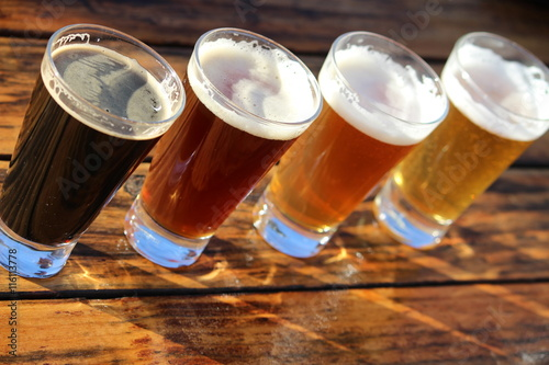 Plagát Four glasses of different craft beers on a wooden table during a tasting