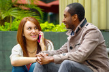 Interracial happy charming couple sitting on steps in front of building interacting and smiling for camera