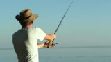 Fisherman on the lake in a cowboy hat.