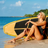 Sexy young woman sitting near a surfboard on the ocean shore