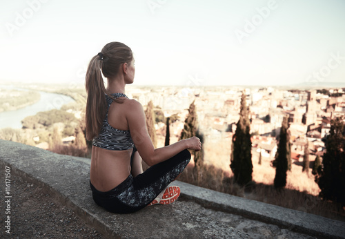 Meditating girl in sportswear sitting on asphalt peak in the country