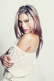 Beautiful young woman wearing off the shoulder knit top. Image cross processed