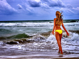 Summer girl sea. Woman in swimsuit on beach near ocean with waves. Sea nature landscape.