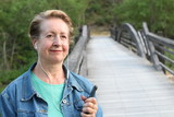 Mature woman waiting your call. Dressing in a denim jacket, a senior Caucasian lady is standing by river bridge, holding a mobile phone, with headphones in her ear