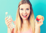 Happy young woman holding apple and water