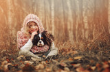 child girl relaxing with her cavalier king charles spaniel dog in autumn forest, wrapped in cozy scarf