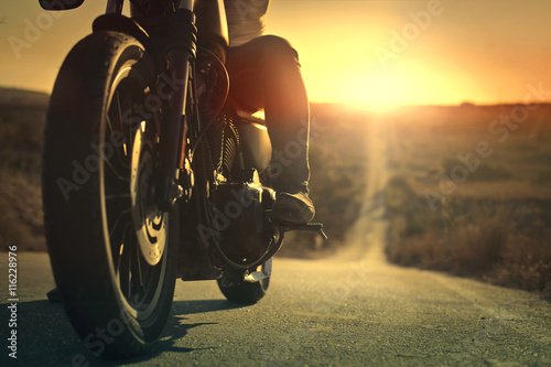 On a roaring motorcycle at sunset плакат