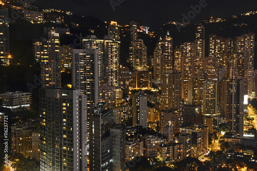 Crowded Hong Kong skyline scene at night with tightly packed skyscrapers and apa