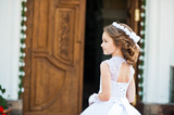 Portrait of cute little girl on white dress and wreath on first - 116238552