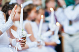 Hands with candles of little girls on first holy communion - 116240319