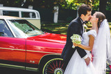 A passionate kiss of newlyweds standing behind old red Dodge