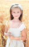 Smiling cute little girl on field of wheat
