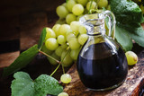 Balsamic vinegar in a glass jug, vintage wooden background, rust