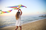 Little girl with flying kite on tropical beach at sunset - Fine Art prints