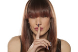 young woman with bangs his finger on his lips. silence gesture