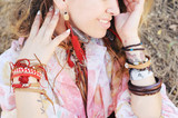 Female neck and hands with boho bracelets and necklace with red