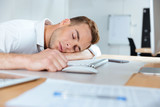 Exhausted fatigued young businessman sleeping on the table