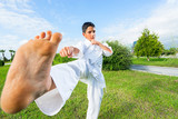 Boy in white kimono during training karate kata exercises in summer outdoors. Selective focus.