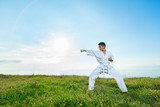 Boy in white kimono during training karate kata exercises in summer outdoors with sky and sea background.