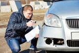 Insurance agent recording car damage on claim form