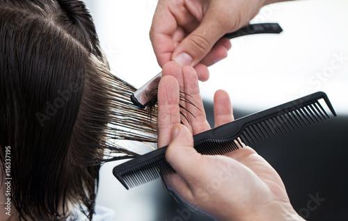 Ścinanie włosów brzytwą, dłonie fryzjera ścinającego włosy