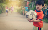 Poor Asian Boy playing with old rustic soccer ball