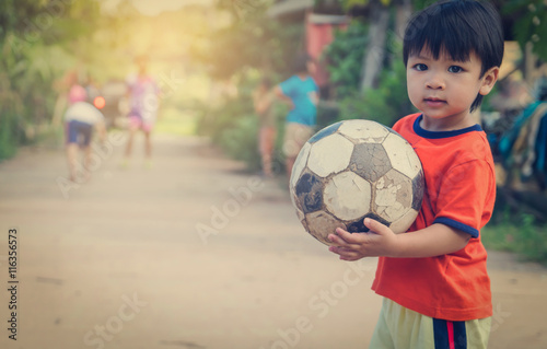 Fotobehang Voetbal Poor Asian Boy playing with old rustic soccer ball