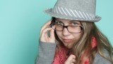 pretty young beautiful woman in a hat and glasses posing