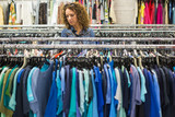 Woman browsing through clothing rails of a thrift store
