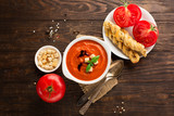 Tomato cream soup with baked tomatoes, red pepper, herbs and spices on dark rustic wooden background, selective focus