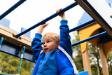 little boy playing on monkey bars in autumn