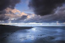 Foto de larga exposición de un fotógrafo profesional en la acción en una hermosa playa en medio de una tormenta durante la puesta de sol.