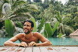 Smiling young man in swimming pool