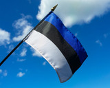 Estonian flag held up against a blue sky with a few clouds. - 116504782