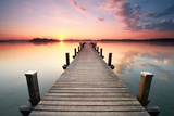 langer Holzsteg am Seeufer zum Sonnenaufgang im Sommer - 116520768