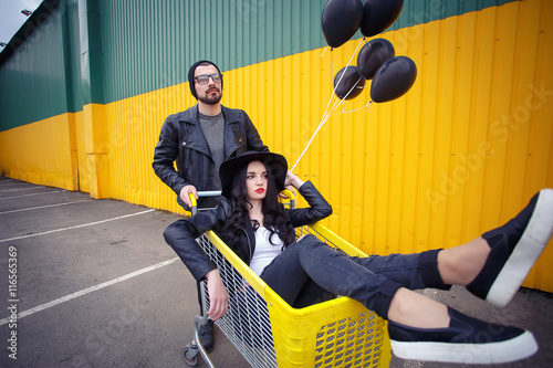Poster Stylish bearded man in black leather jacket and jeans and a girl with long black
