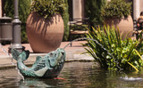 Relaxing zen fountain in a koi pond with plants and fish in a garden. - 116573910