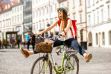 Young female tourist with backpack and hat having fun riding a bicycle in the old city center of Ljubljana in Slovenia - 116600380