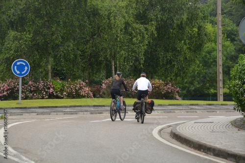 pareja de ciclistas circulando por la carretera
