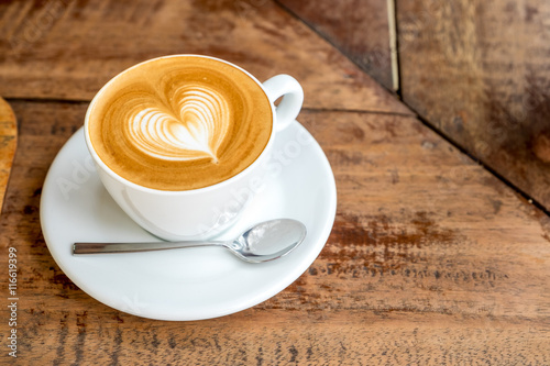 Wall mural Close up white coffee cup with heart shape latte art on wood tab