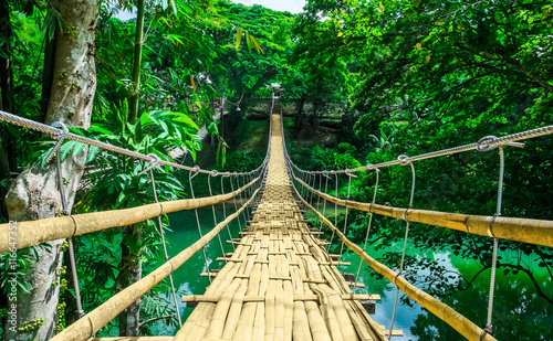 Fototapeta Bamboo hanging bridge over river in tropical forest