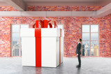 Businessperson looking at huge gift