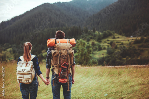 Poster A couple hikers Hiking with backpacks walk along a beautiful mountain area holding hands