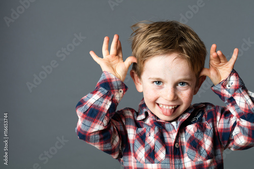 smiling young kid sticking out his tongue, playing with hands Poster