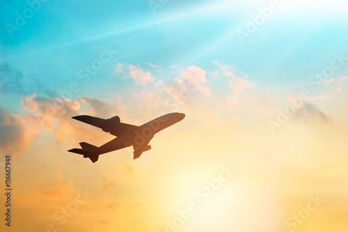 Airplane in the clouds sky in sunset, pastel color