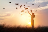 Woman praying and free birds enjoying nature on sunset background - 116669310