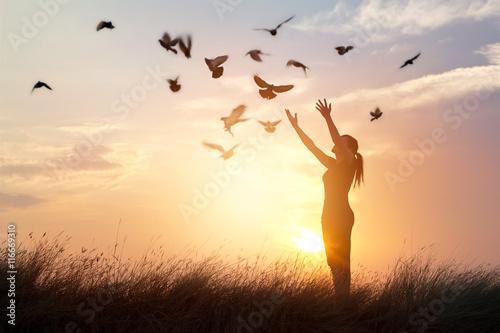 Poster Woman praying and free birds enjoying nature on sunset background